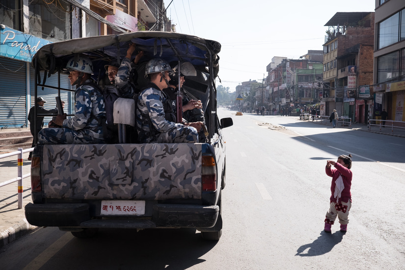 A girl wanting to play with officers from the Nepal Armed Police Force (APF) who were in a police vehicle waiting by the side of the road, during a protest along Pulchowk road in Lalitpur, Nepal.